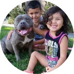 Dixie's two youngest human family members smile beside Dixie, who has a big dog-smile on her face. Spay Day Sacramento